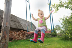 pleased-toddler-girl-wearing-red-kids-gumboots-riding-handmade-rustic-swing